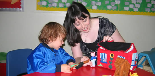 Woman and child interacting at nursery