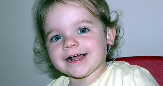 Young girl wearing cochlear implant